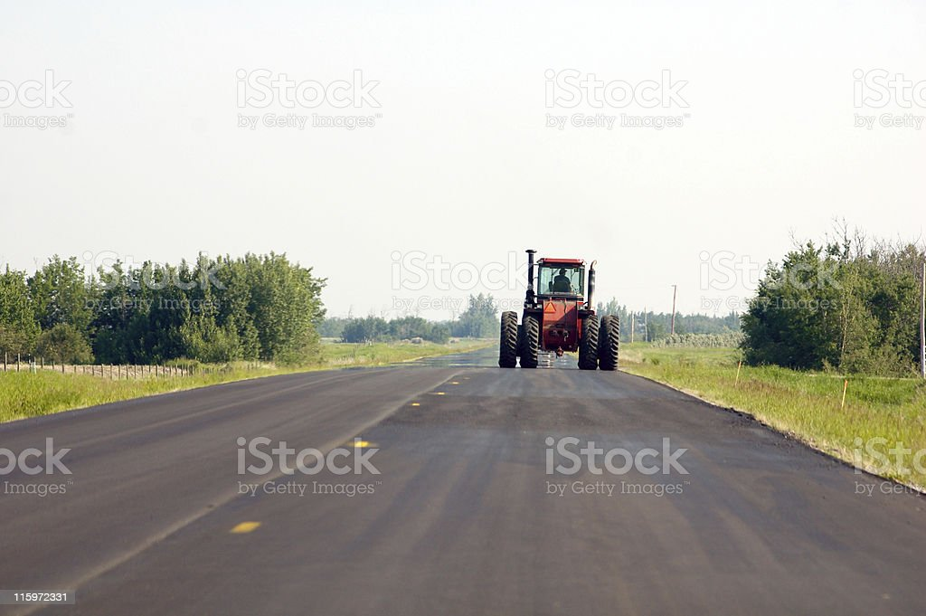 Large Tractor Driving Down Country Road stock photo
