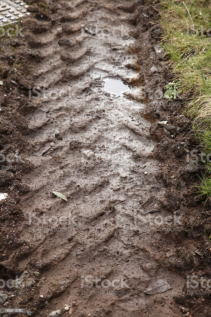 Large tractor tracks in soft wet mud royalty-free stock photo
