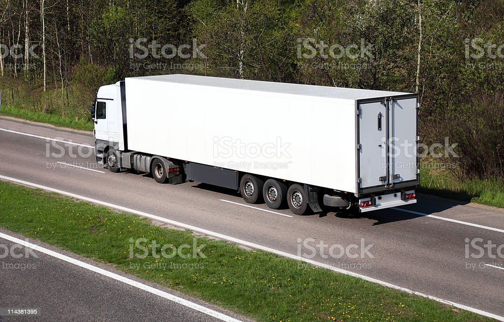 large truck driving on country highway stock photo
