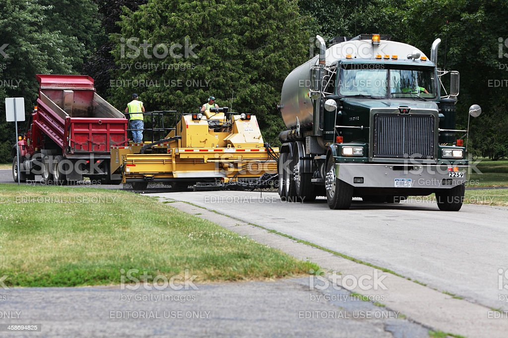 Workers using large trucks and a specialized automated gravel...