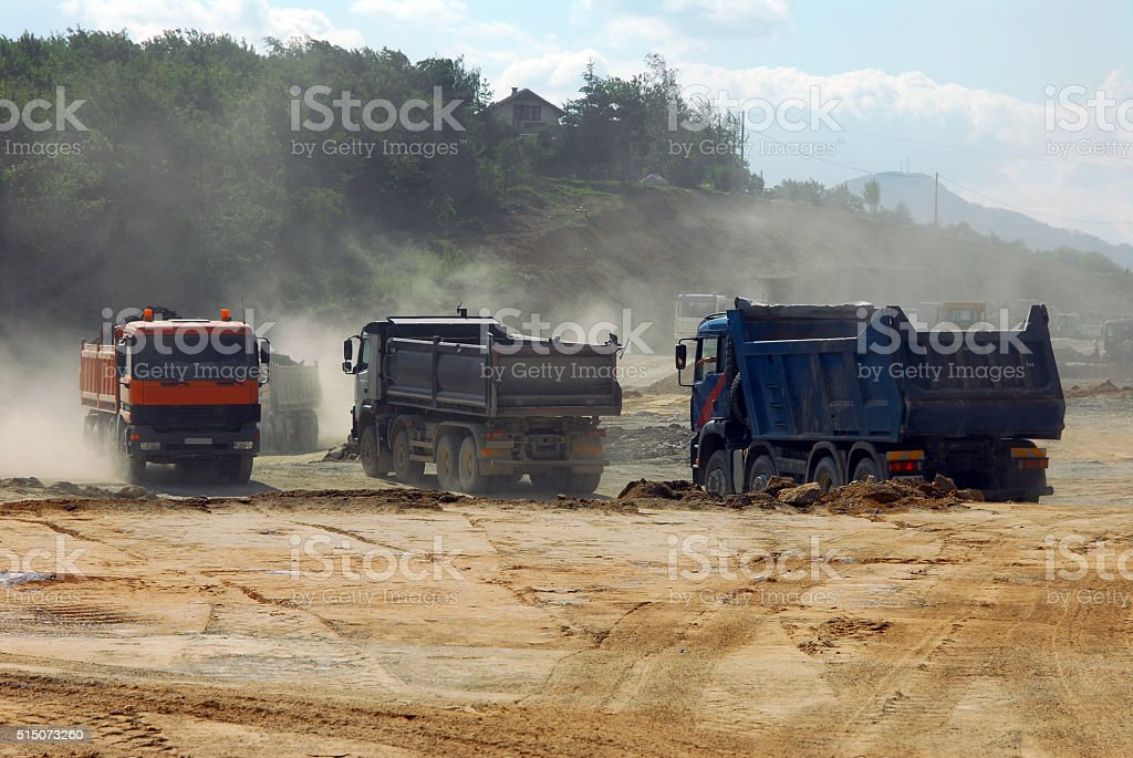 large trucks at construction site stock photo