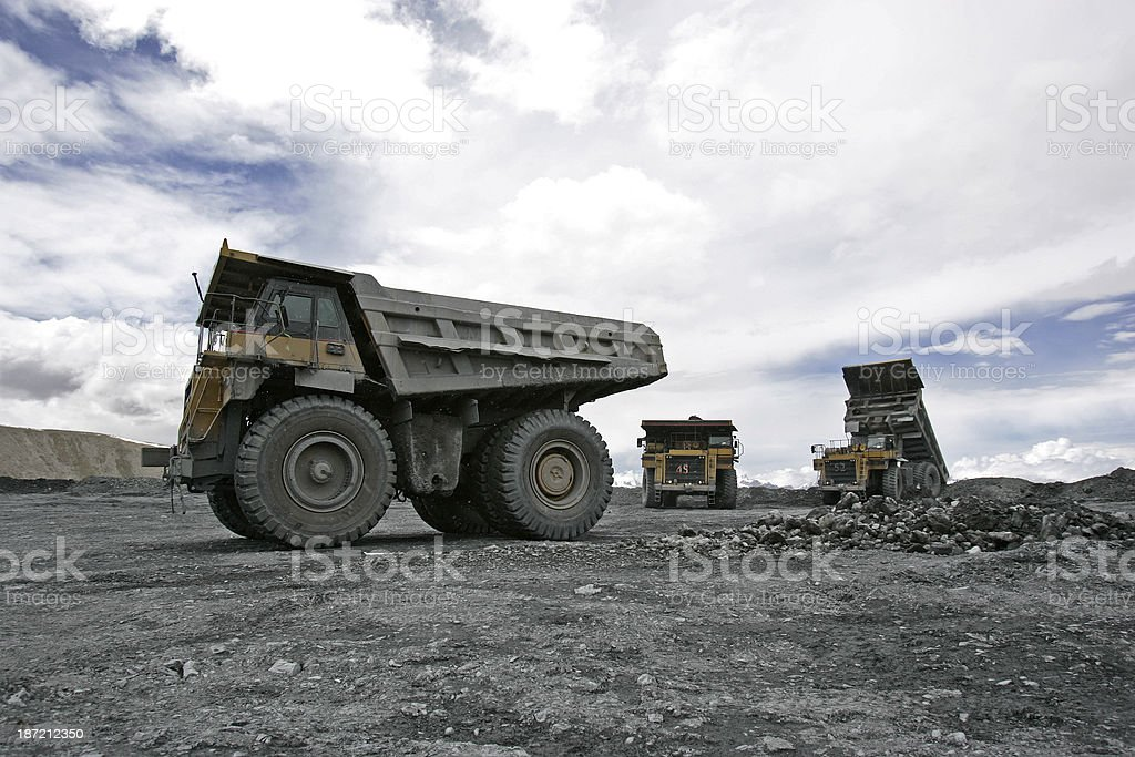 Large trucks dump gravel at a mountin gold mine