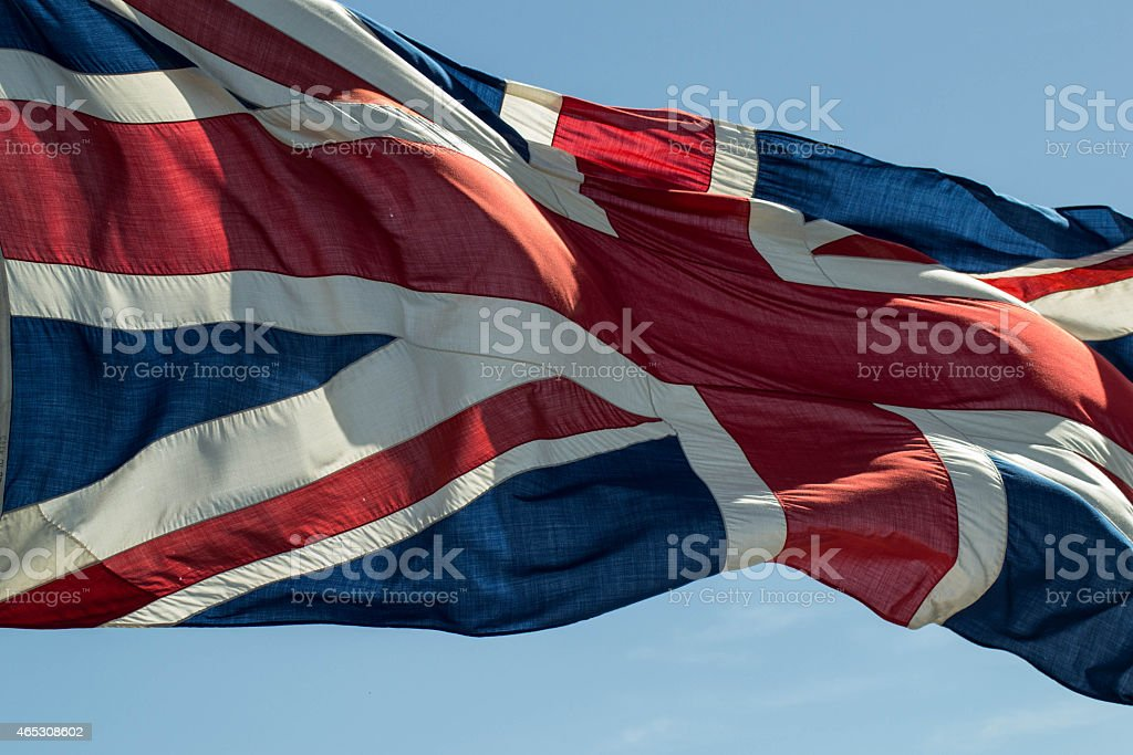 Large Union Jack flying with blue sky stock photo