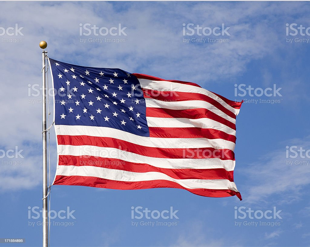 Large US flag blowing against blue sky stock photo