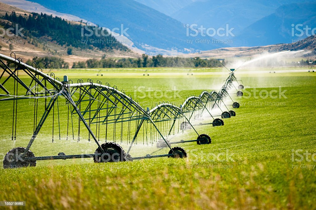 A large wheeled irrigation system in a field stock photo