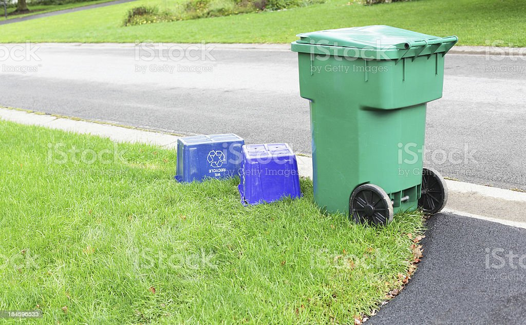 Large Wheeled Waste Container and Two Empty Blue Recycling Bins royalty-free stock photo