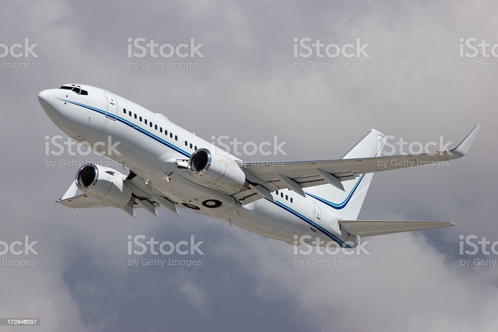 Large white airplane flying high among the clouds stock photo