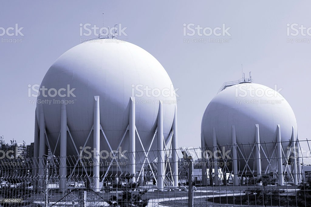 Large white circular storage tanks at a natural gas facility royalty-free stock photo