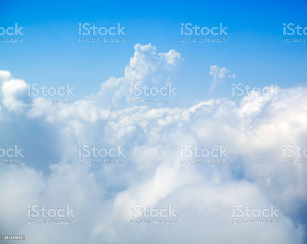 Large white fluffy clouds set against a bright blue sky royalty-free stock photo