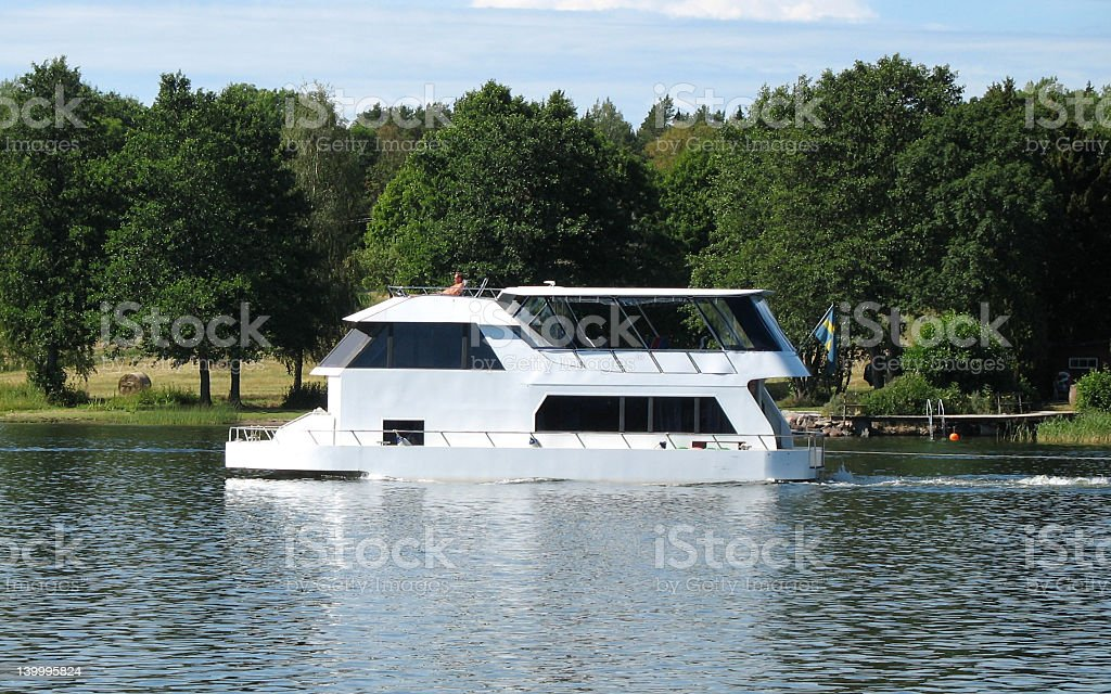 Large White House boat moving across the lake royalty-free stock photo