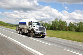 Large, white propane truck driving alone on highway road