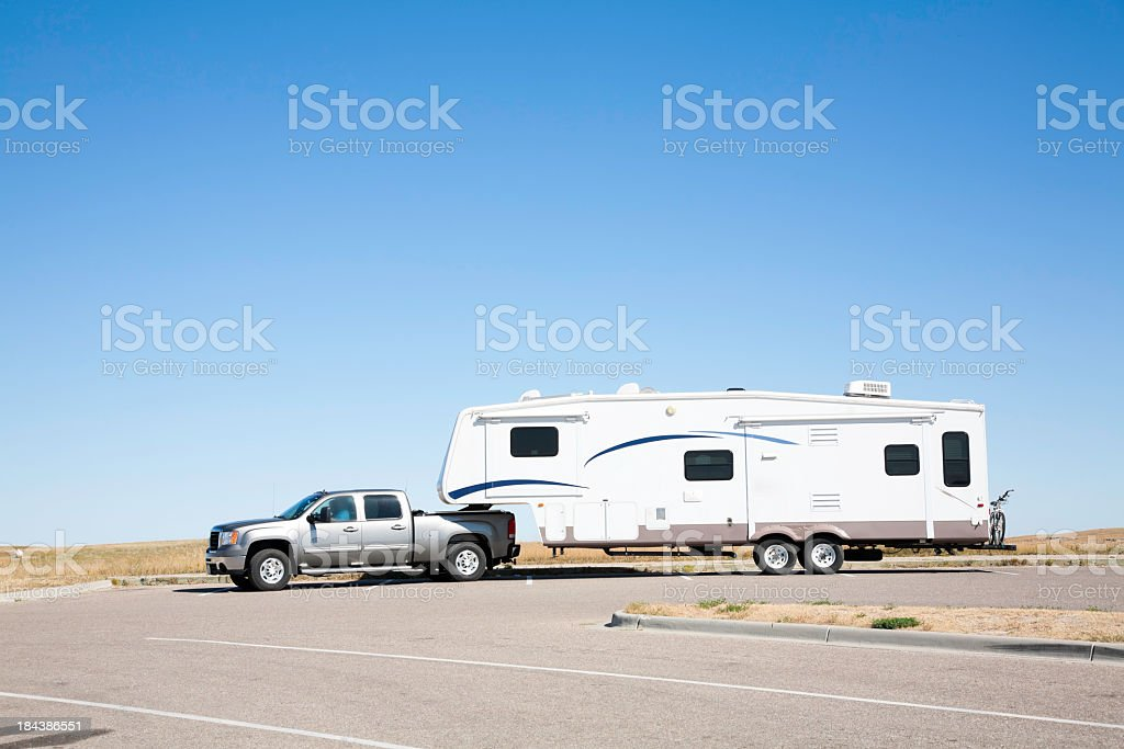 Large white RV trailer hitched to a double cab gray truck stock photo