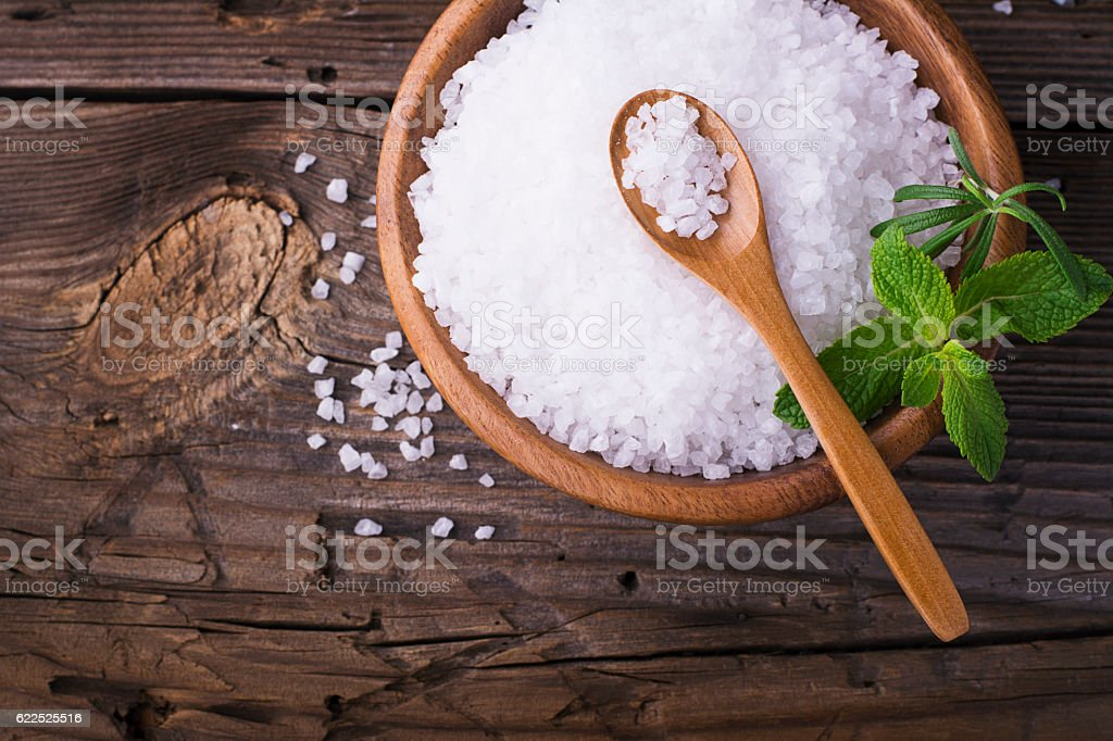 Large White sea salt in a natural wooden bowl with stock photo