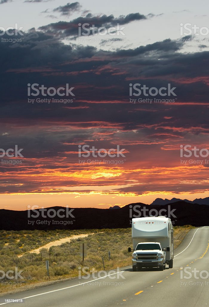 A large white truck driving down a road at sunset stock photo