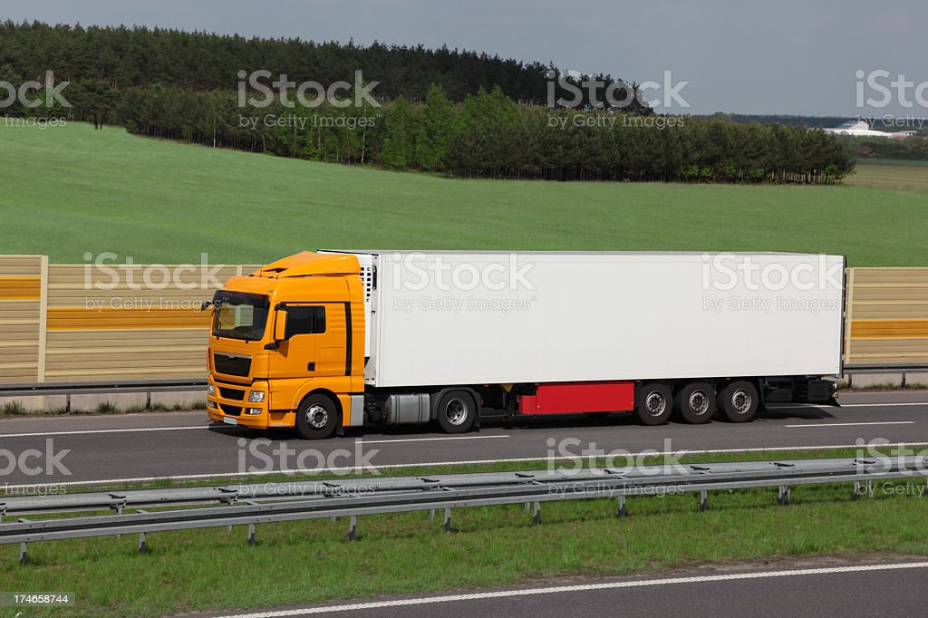 A large yellow truck on the highway royalty-free stock photo