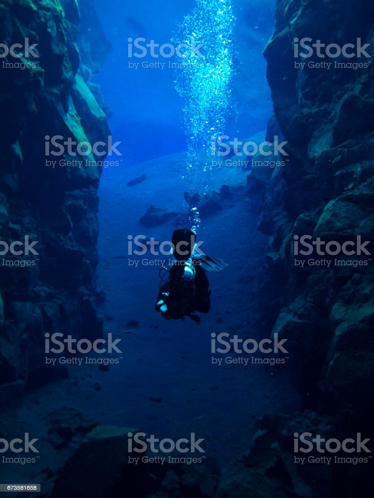 Larger View of Single Scuba Diver with Bubbles in Continental Split at Silfra in Deep Section at Pingvellir National Park stock photo