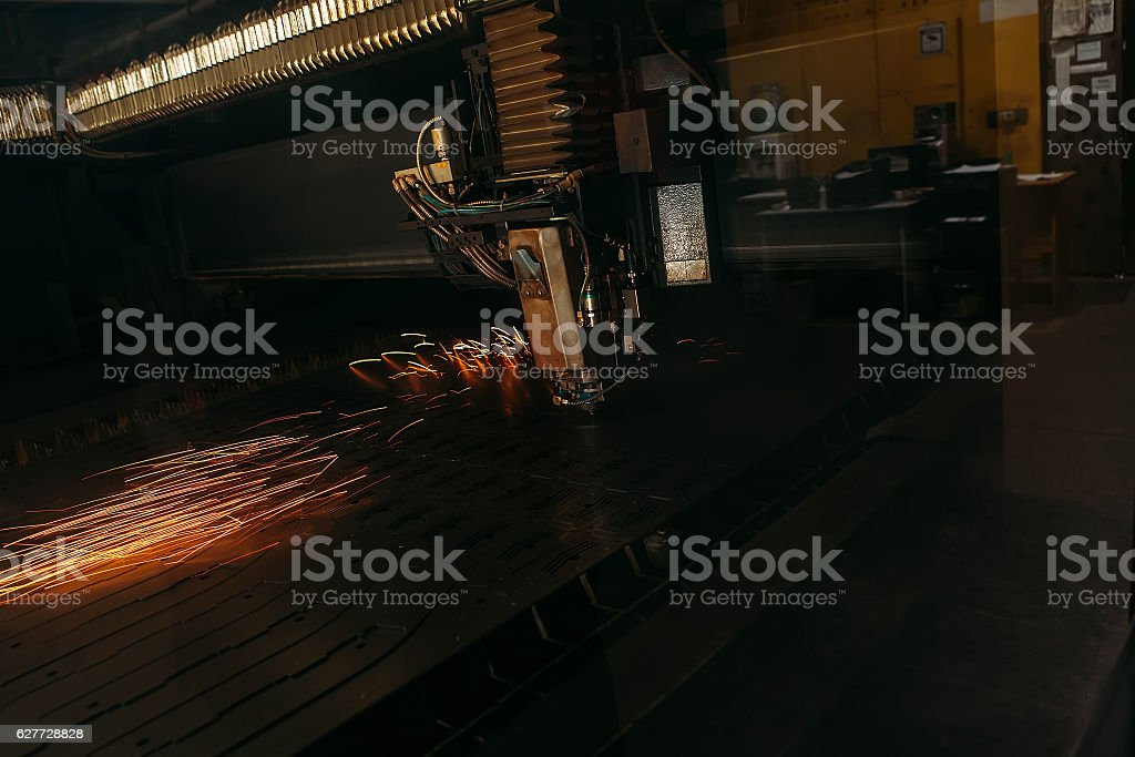 Laser cutting machine cuts the metal with sparks stock photo