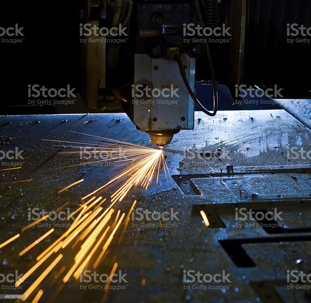 Laser cutting metal close up, sparks flying stock photo
