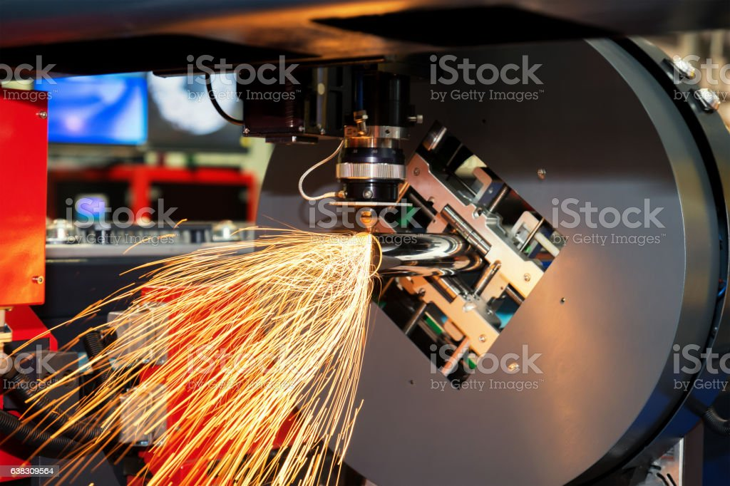 CNC laser cutting metal pipe with bright sparkle in factory. stock photo