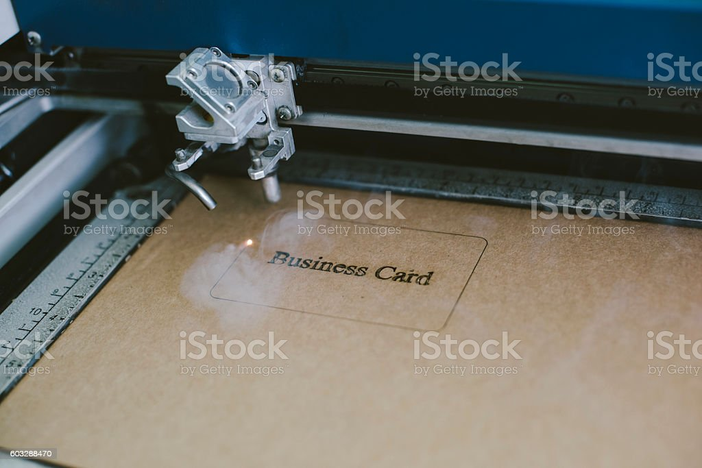 Laser engraving business card from recycled cardboard stock photo