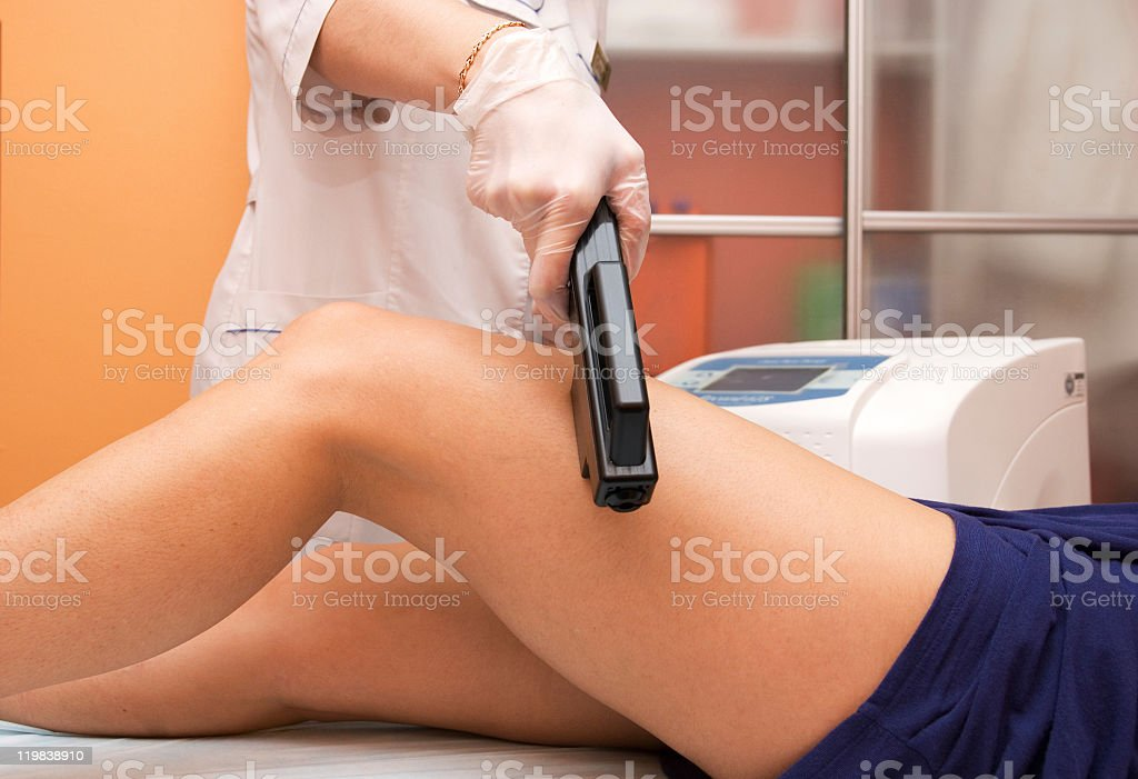 Laser hair removal on woman's leg royalty-free stock photo
