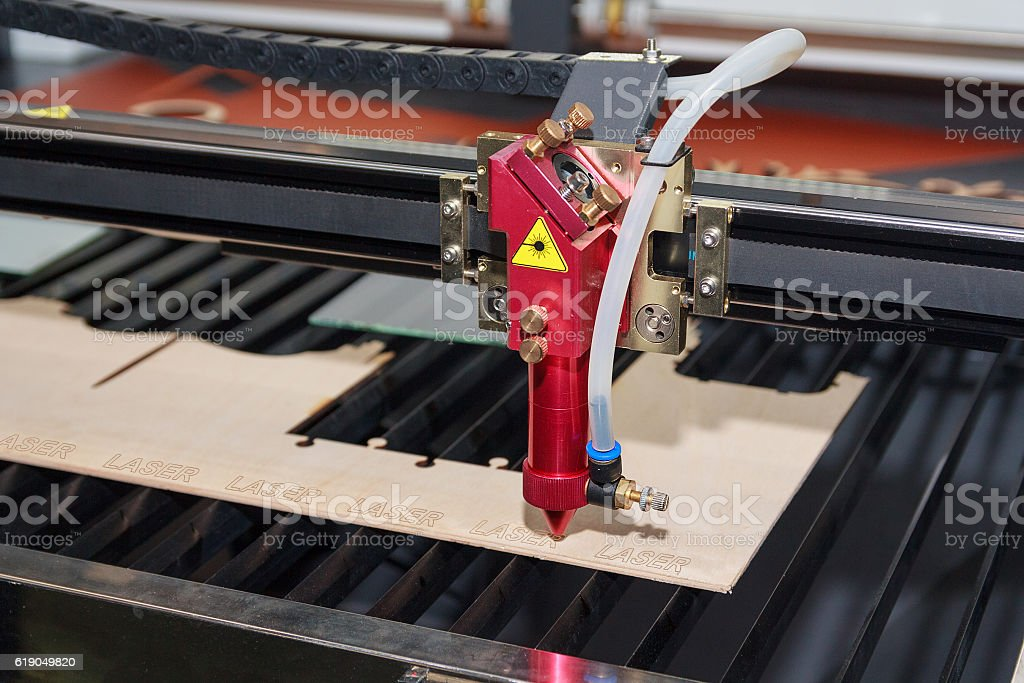 Laser machine for cutting and engraving plywood. Industry stock photo