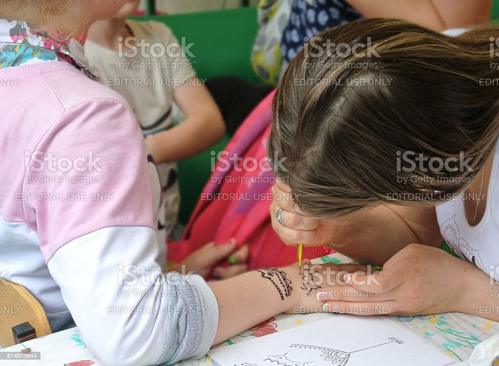 lass volunteer project 'Good Works' makes temporary tattoos on girl stock photo