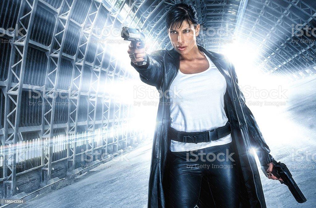 Beautiful female action hero, shooting at her enemies in abandoned...