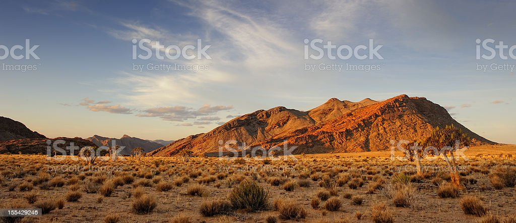 Last light on desolate rock formation and quiver tree forest stock photo