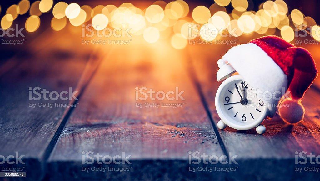 Last Minute Christmas - Alarm clock Santa Hat Defocused wood stock photo