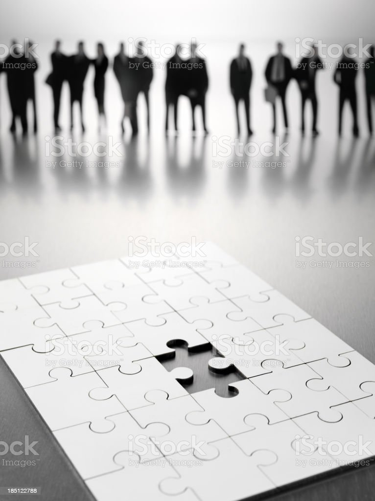 Last Piece Missing in a Puzzle with Business People royalty-free stock photo