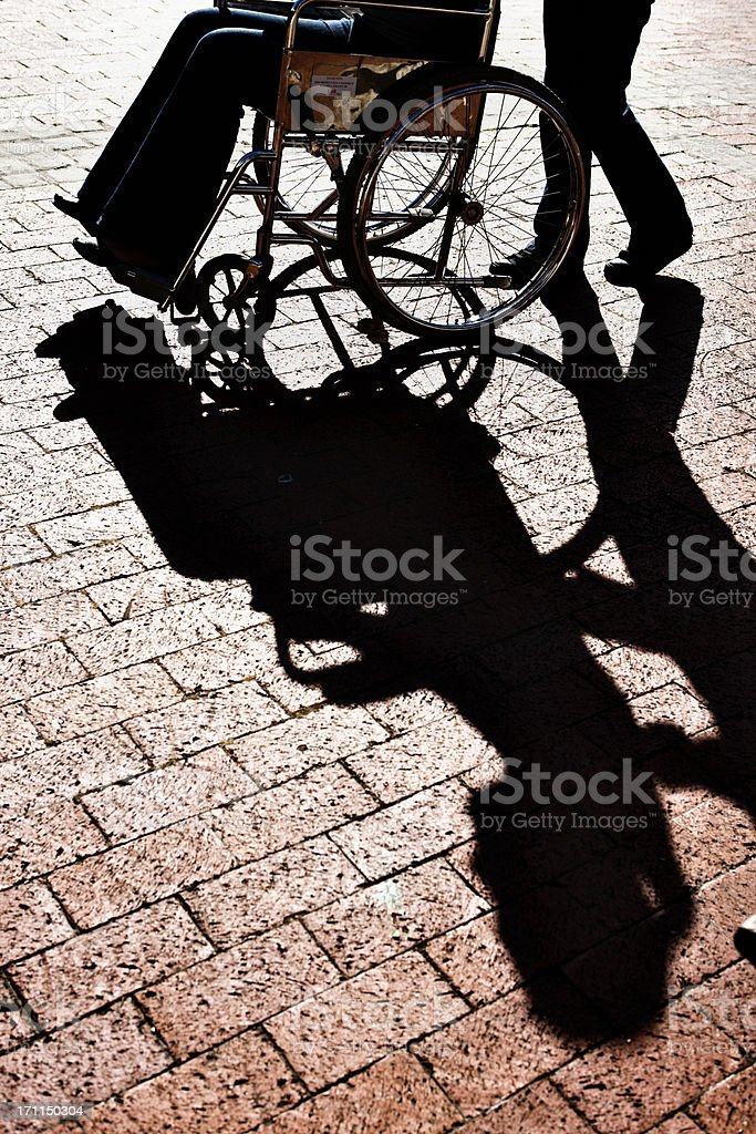 Late afternoon shot of wheelchair being pushed across paving royalty-free stock photo