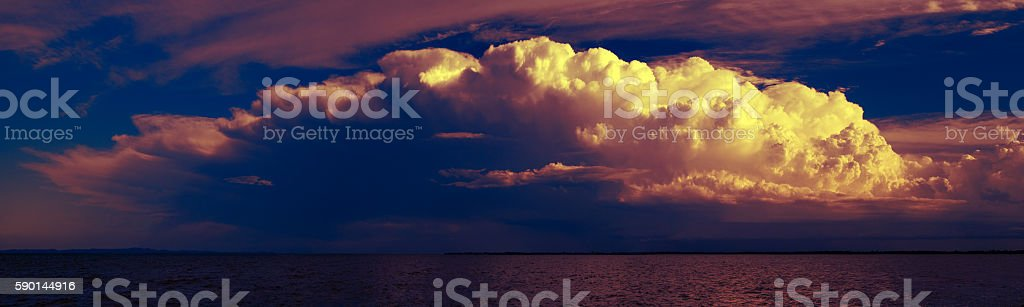 Late afternoon thunderstorm lit by the setting sun stock photo