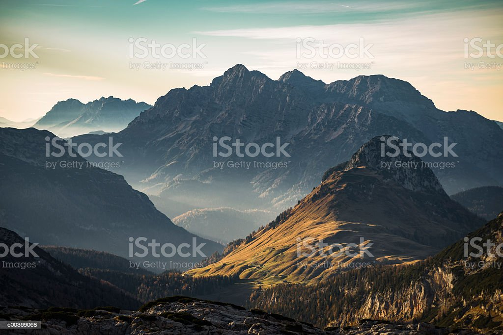 Late autumn sunset with warm sunlight on alpine pastures and the...