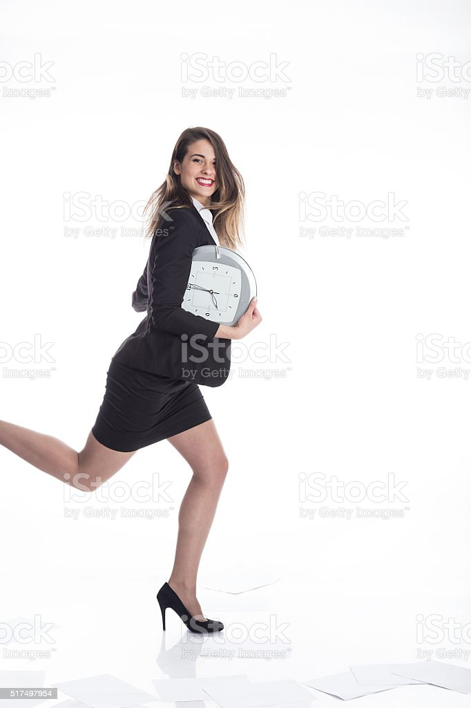 Late busy business woman running against time with smile stock photo