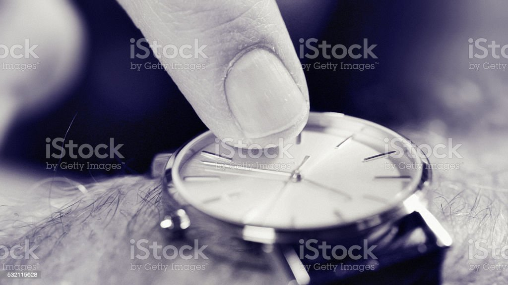 Late, deadline, overdue, or curfew: irritated male finger taps wristwatch stock photo