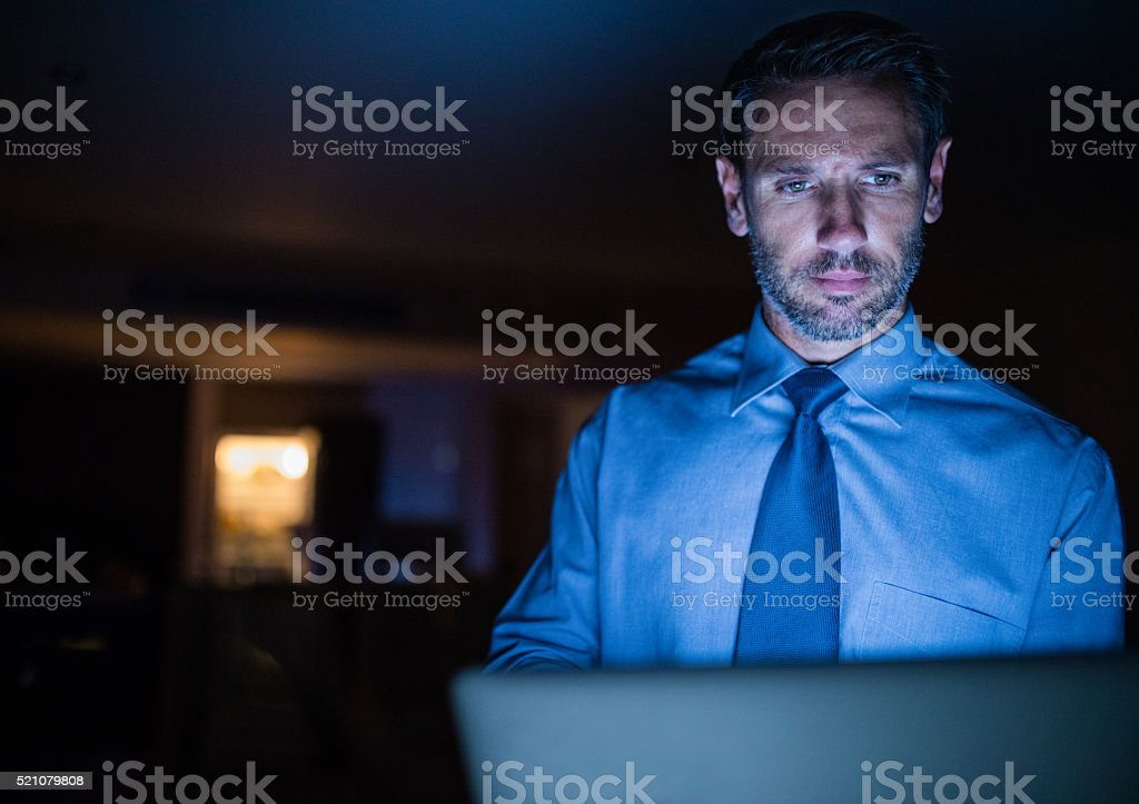 Late night working man using laptop in the dark stock photo