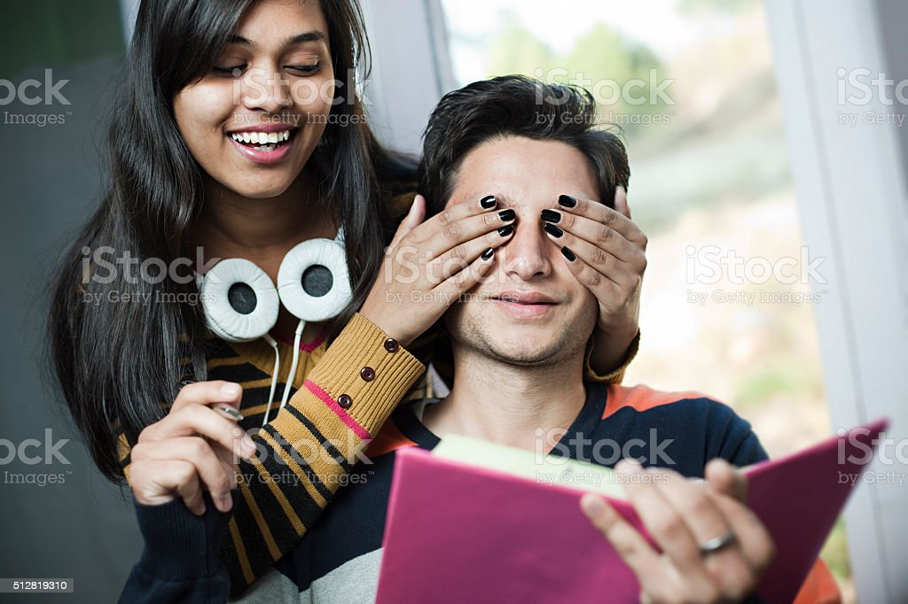 Late teen girl covering eyes from behind of her boyfriend. stock photo