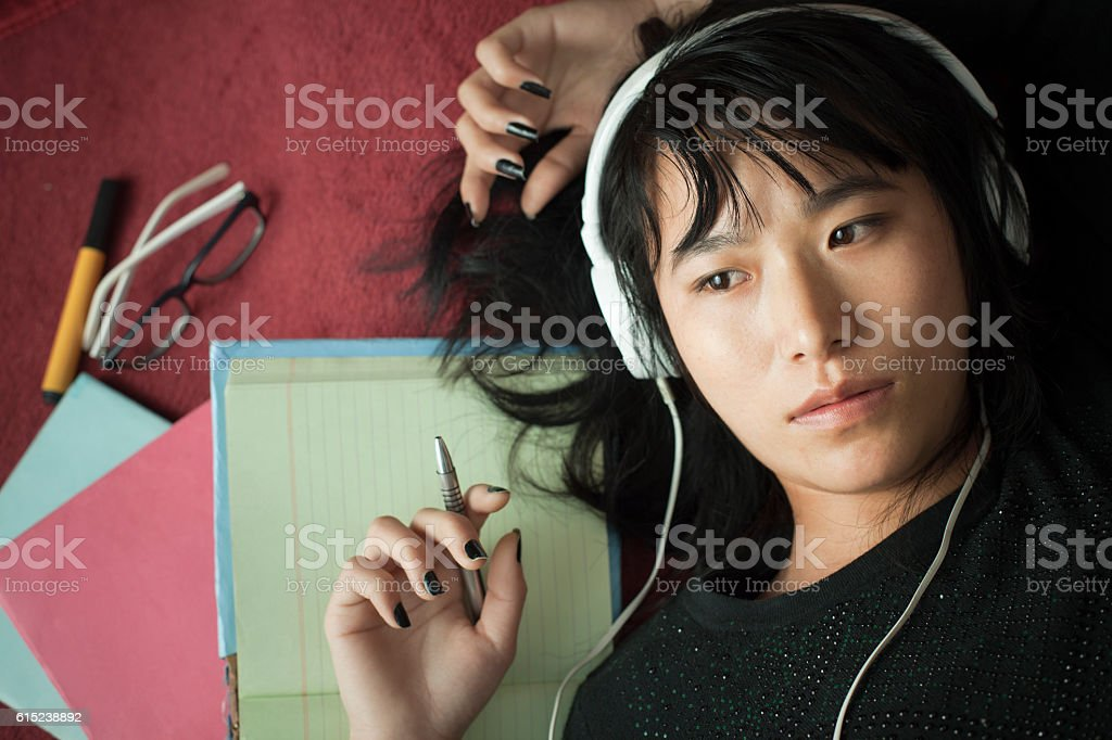 Late teen girl student listening music and reclining on carpet. stock photo