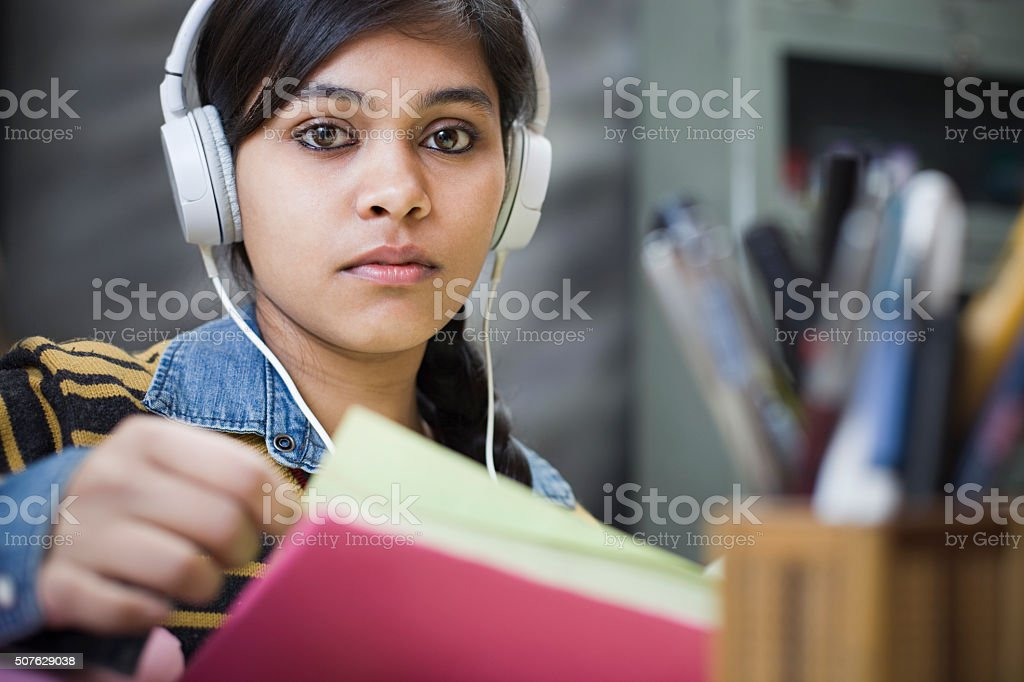 late teen girl student studying and listening music. stock photo