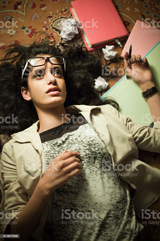Late teen girl student thinking and reclining on floor carpet. stock photo