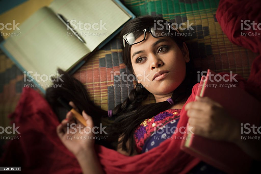 Late teen girl student thinking and reclining on floor mat. stock photo