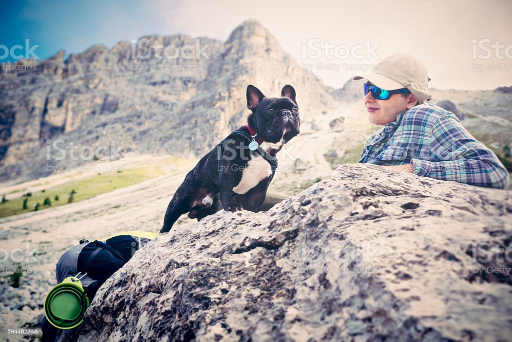Late teen relaxing with dog at mountain pass, Dolomities stock photo
