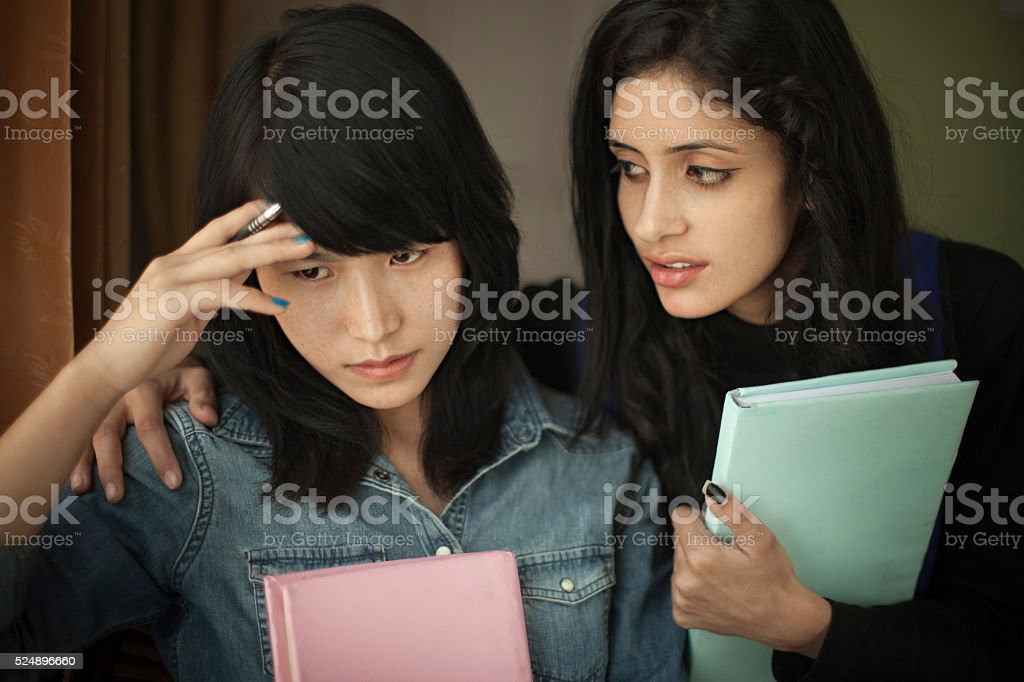 Late teen student consoling to a depressed friend while studying. stock photo