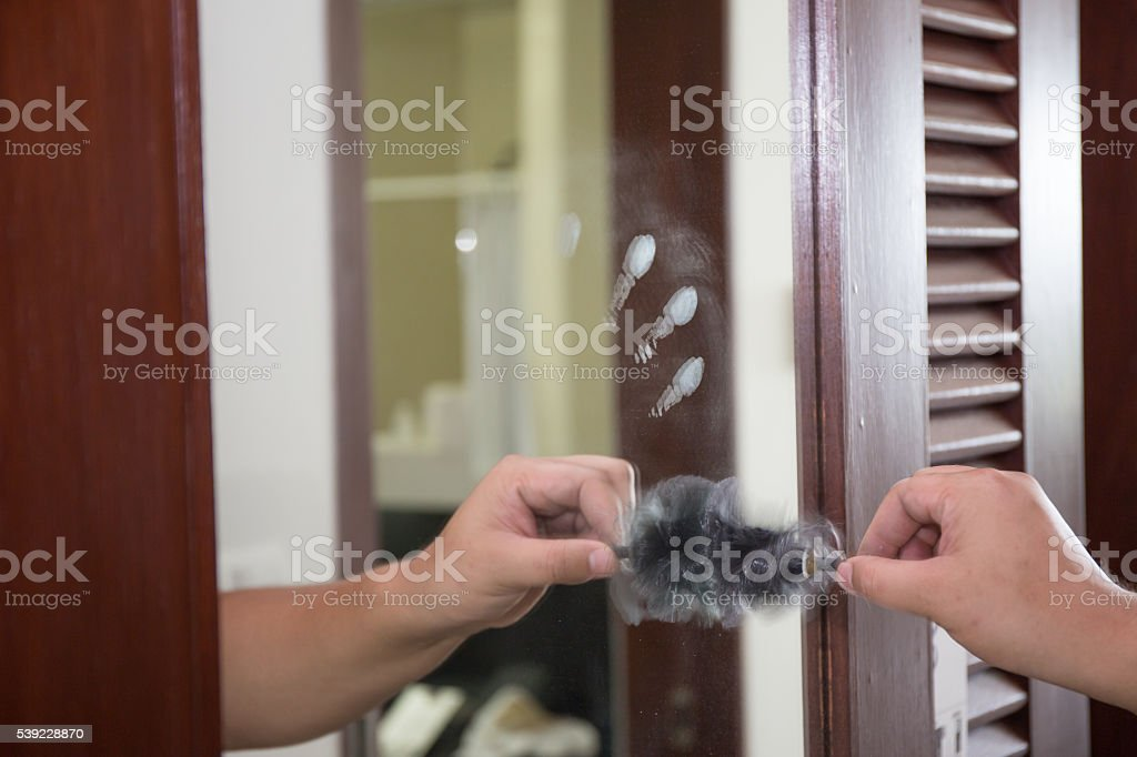latent fingerprint searching by forensic hand stock photo