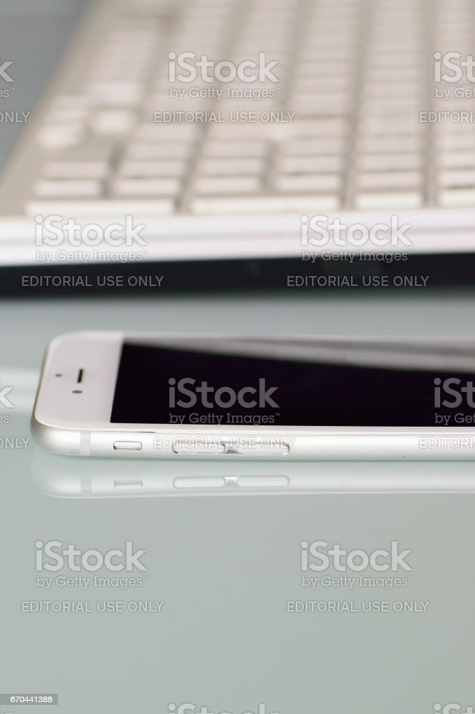Latest iPhone on desk in vertical frame with blurred laptop PC keyboard in vertical frame stock photo