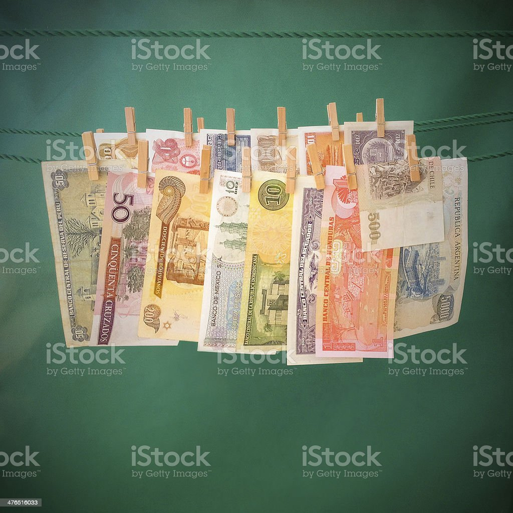 Latin american currencies hanging from clothespin stock photo