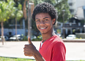 Latin american guy with dental braces showing thumb