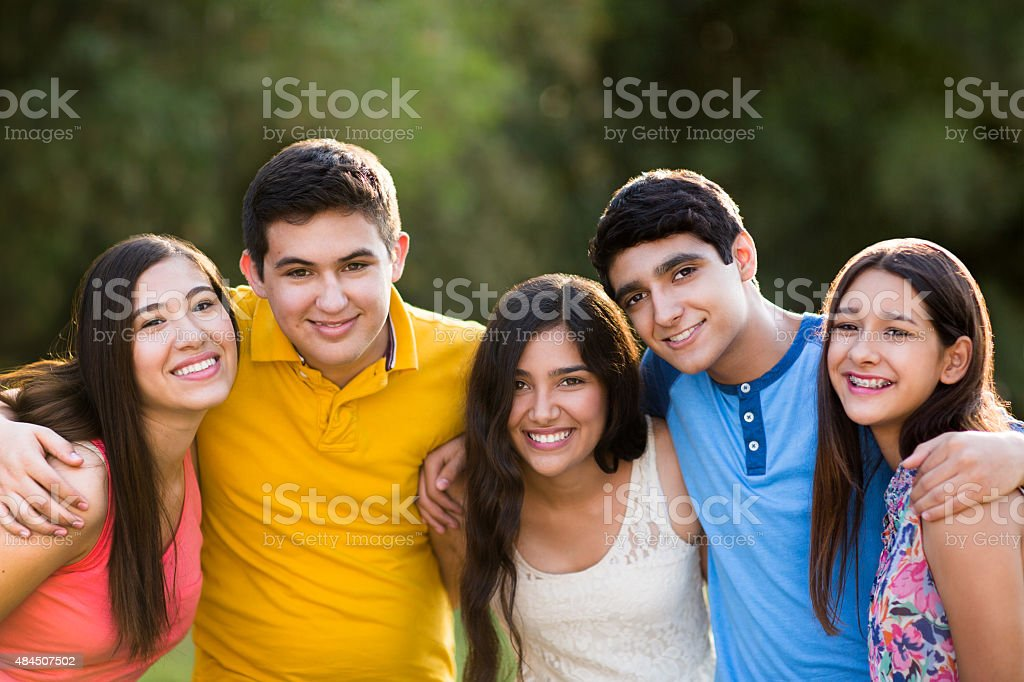 Latin American young friends in park stock photo
