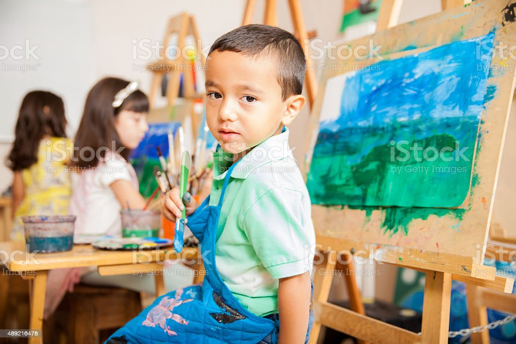 Latin boy painting in art class stock photo